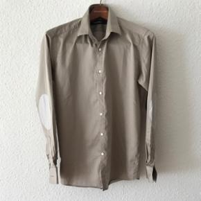 Cool skjorte fra Lagerfeld i sølv/grå farve med signatur knapper og albue patches. Købt i Herrernes Magasin i sommers. Benyttet 2 gange og fejler intet. Kostede 1.199kr