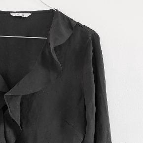 ENVII blå om bluse i sort med en luknings knap ved barmen, den er sort med små prikker på, se de næste billeder for at se stoffet nærmere, den er gået lidt ved hullet hvor snoren skal igennem men den er ikke gået i stykket   Størrelse: S   Pris: 100 kr   Fragt: 39 kr ( 37 kr ved TS handel )