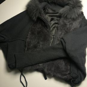 Mega fedt strik overgangs jakke/ trøjr i grå strik med grå kanin  og med grå ræv på kraven. Den har stik lomme, lynlås samt snoretræk i underkanten. Købt i Berlin i designer butik. men ved ikke hvem der har designet den, da jeg ikke er så god til mærker der kradser i nakken.
