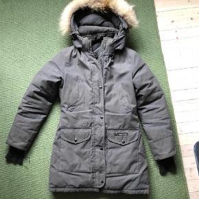Varetype: Dunjakke Farve: Grå  Varm og lækker kvalitets vinterjakke. Brugt nogle sæsoner og trænger til at komme til rens. Der er en lille malerplet på bagdelen og elastikkerne ved hænderne er slidte. Ellers en super dejlig frakke.