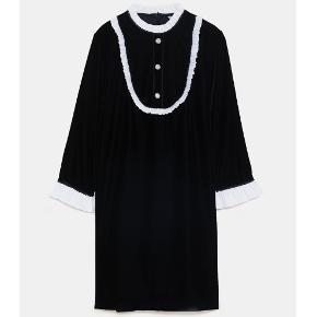 ALDRIG BRUGT! Mærke sidder stadig på.  Str. M. NYPRIS 449kr.  Sort lårkort kjole i velour med høj krave, ærmer med hvide manchetter i stof, flæser på bryststykket, fine smykkeknapper og skjult lynlås bagpå.   (Modellen, der har kjolen på, er 178cm).