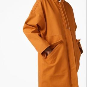 """Monki frakke i flot olivengrøn farve. Str. M-L. (Oversize i størrelsen). """"A below-the-knee length cotton jacket with a hoodie, classic drawstrings and roomy front  pockets."""" ALDRIG BRUGT! (Billeder af den orange, for at vise modellen på. Min er bare OLIVENGRØN)."""