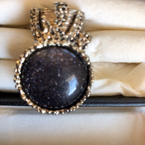 Fin ring i guldfarve og med mørk sten med fint guldglimmer. Ringen er kun sparsomt brugt og der er ikke slitage. Måler ca. 4 cm. og indeni svarer den til en M-L (ca. 1,7 cm).   BYD gerne, sender med Dao på købers regning.  Bytter ikke.