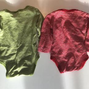 Varetype: Uldbody i uld silke Farve: Rød stribet  Kun rød tilbage. Virkelig lækker body i uld og silke, helt uden pletter, huller og vaskefnuller. Vasket skånsomt i uldvask og er som ny. Til nyfødt størrelse 50/56.