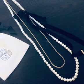 Fin halskæde med perler og et bindebånd, og en guld kæde. Kan pifte ethvert look up.