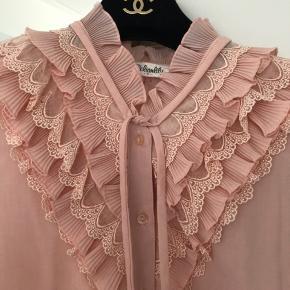 Så smuk vintage skjorte, købt i Frankring, sælges. Minder om Stine Goya i style og feminine udtryk! Skjorten har den smukkeste lyserøde pastel farve og fine ruffle deltaljer. Der er ingen størrelse eller materialelabel i, men den tilsvarer en S/36 og materiale er sandsynligvis en blanding af bomuld samt polyester. Skjorten har et lille hul i den ene side nederst (se billeder) - dette ses ikke, hvis skjorten fx er nede i bukserne, og kan ellers fixes med nål og tråd. Pris: 450kr afhentet eller plus porto.