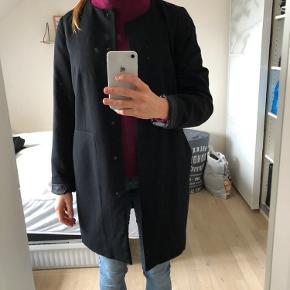 Den fine lette jakke fra Vero Moda i sort. Med Knaplukning og to store lommer.  I meget fin stand. Str. hedder M.