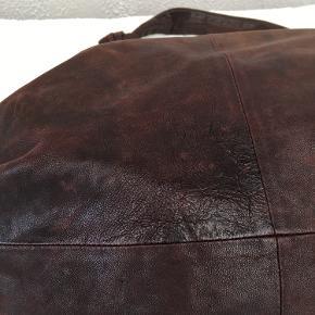 YVONNE KONÉ BUMBAG  Bumbag'en er brugt nænsomt, hvorfor læderet på fineste vis er patineret. Tasken har et smukt farvespil (se foto 2), hvilket giver et helt unikt look.  NB: farven er dyb violet
