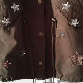 Overgangsjakke fra Zac & Zoe i farven Khaki/Armygrøn. Sød Jakke med palliet-stjerner. Helt ny. Kan reguleres og 'spændes' i livet og forneden på jakken, som giver et fedt look.