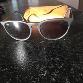 Solbriller fra Ray-Ban. Små i str. Alt medføres. Hylstret har en revne fra brug som kan ses på billedet, pudsekluden er ikke i brugt stadig i plastik. Købt på en amerikansk hjemmeside, så har ikke kvitteringen. Nypris 1000 kr.