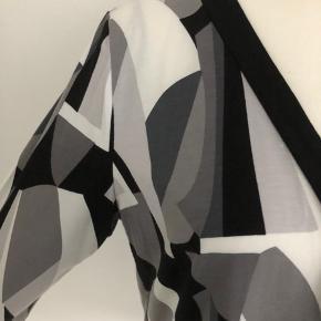 Flot bluse fra Paprika med motiv i hvid, grå og sort. Ærmerne er 3/4 lange.  Længde fra skulder er 72 cm, og brystmålet er 116 cm.  Fremstillet af 95% viscose og 5% spandex.  Bærer ikke præg af brug.