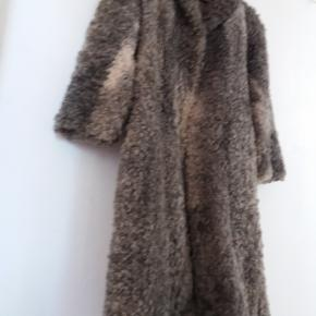 """Vintage frakke pels i en sjælden smuk og krøllet lammepels. Syet i prinsessesnit, """"princess coat"""". Farverne changerer så fint i skindet, som mange gode år i sig endnu. Skindet ligner mest Gotlandsk lam og er ikke astrakan.  I foret er der nogle huller og plet, men foret er dog stadig brugeligt - pelsen er dog så lækker, at den vil være værd at sætte et nyt for i. Størrelsen passer en str. small/36.  Sælges for 1.200kr. pp. Sendes med DAO"""
