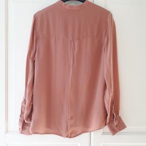 Skjorte fra Samsøe & Samsøe i str. s, med åben slids på ryggen.  Materiale 100 % silke.  Hentes i Roskilde eller sender med DAO mod betaling af fragt.