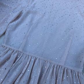 Flot fersken farvet sommerkjole fra Moves by Minimum med fine gulprikker. Kjolen har rundhalsudskæring foran, der ender i en v-udskæring bagpå. Kjolen kan sagtens vende begge veje. Kjolen har 3/4 ærmer med flæse i bunden.
