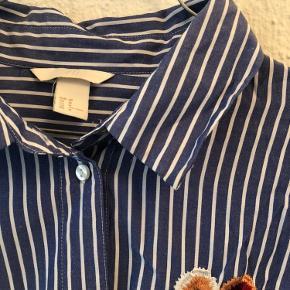 Smuk klassisk skjorte i striber og med flotte blomster broderet på.  Oversize fit.