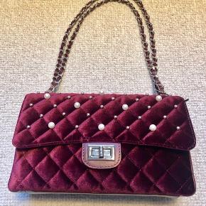 Smart quiltet taske fra Italien, med kæderem. Kan laves i 2 længder. Indvendig skillerum og lynlås inderkomme. Beklædt med små perler på front. Findes også i vinrød og rosa.  Længde 27cm højde 16cm dybde 9cm. Ny pris 999,-