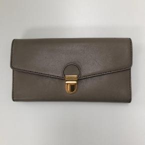 Varetype: Pung Størrelse: 19,5 cm x 10cm Farve: Brun Oprindelig købspris: 1500 kr.  Pungen er lys grå/ brun. Den indeholder plads til6 kort, mønster samt tre rum til div. Pungen har let patina på spænde og læder.