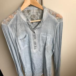 Flot lyseblå skjorte med glimmer og sten (stjerner) - blonde ryg