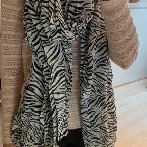 Stort tørklæde med zebra print. Syningen er gået lidt op nogle steder i enderne - se meget gerne billede. Der er ikke syning i siderne.