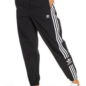 Adidas Originals  -trefoil logo på hoften. - 3-Stripes på siderne. - Sidelommer. - Manchet i taljen samt ved anklerne.  Materiale: 100% Polyester.  Stadig med mærke. Giv et bud