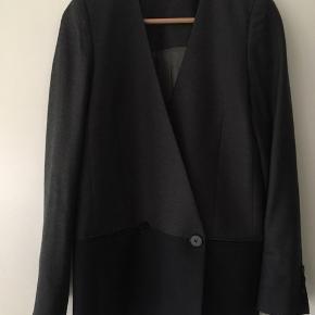 75% Virgin wool/ uld oversized blazer. To-tonet i mørke- og lysegrå. To lommer fortil. Brugt en håndfuld gange og i fin stand.