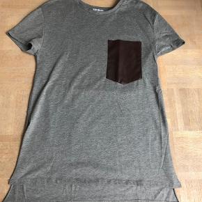 Varetype: Flot ny T-shirt med læderlomme Farve: Grå Oprindelig købspris: 349 kr.  Lækker T-shirt med brun læderlomme og slids i siderne. Kan afhentes i Århus C. eller sendes. Kun vasket ved køb men aldrig brugt. Prisen forudsætter mobilepay.