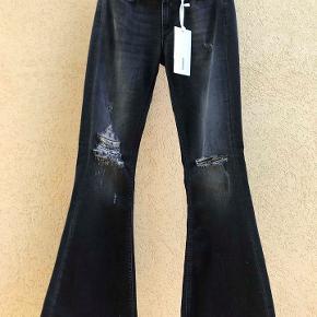 Super seje Dunlop flared jeans str. 28. Aldrig brugt, med tag.  Flot sortblå farve. stretch, med rå kanter forneden. Porto 38 kr. Nypris 2000.- Kan ses i Rungsted