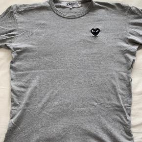 Commes des garcons Basic t-shirt i grå med sort hjerte og hvide øjne Er XL men passer som M/L Nypris 700,-  Prisen på 300 er ikke til forhandling. Take it or leave it. Jeg kan også sagtens beholde den :)