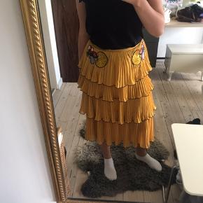 Maxi nederdelen er fra mærket Delfi. Den er gul med sorte detaljer i enden af dens lag. Og to flotte blomster i toppen af nederdelen. Den er praktisk talt så god som ny, da jeg kun har gået med den 1 gang. Byd gerne.