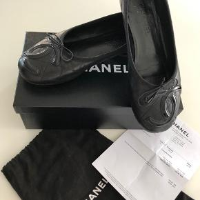 Chanel ballerinaer (model Cambon) i sort kviltet skind med lak CC logo på front. Str 38. Super behagelige men må nu endelig erkende at modellen desværre er for stor (og dermed også for bred) til min (smalle) fod - jeg bruger normalt str 37,5. Købt i 2012 i Frankfurt for EUR 440 (ca DKK 3300).  Jeg har brugt dem (ofte med en indlægssål) - og de er i super flot stand. Eneste synlige tegn på brug er i kantbåndet ved hælen (se billeder). Det er dog først noget jeg har opdaget her ifm billedtagning og er således ikke noget man bemærker ved brug. Æske, kvittering og dustbag medfølger ved køb.  Bud er velkomne - og jeg sender med dao. Køber afholder TS gebyr og porto - men jeg handler gerne via mobile pay.