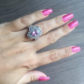 Ring med gennemsigtige og lyserøde sten. Ringen er ikke ægte sølv. Ringen måler ca. 1.65 cm i indvendig diameter.