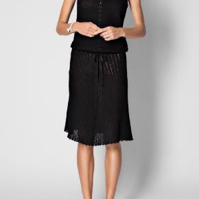 Elegant kjole med et karakteristisk symmetrisk strikmønster, som giver kjolen et romantisk look. EMBRY har et feminint snit med fremhævet talje og elegant v-udskæring både foran og bag. Bindebånd i taljen, som kan justeres. Let og blød kvalitet af 100% llama-uld.