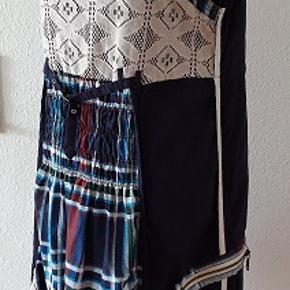 Kjole fra Desigual . Masse af smukke detaljer Kjolen lukkes bag på med lynlås . To lommer på begge sidder af kjolen , to lynlås som pynt.  Bred elastik i taljen .Taljen kan reguleres med fint bånd . Lille spænde bag  på . Fine stropper. Typisk  Desigual kjole med  logo og påtegninger  i forskellige steder. Størrelse  44  Materiale :  99% Cotton (bomuld)  , 1 % Polyamid Brugt 1 gang , er fuldstændig som ny . Længde målt bagfra -  89 cm Brystmål - 105 cm  (elastik som strækker lidt) Oprindelig  pris  var 899  kr  Du skal klikke på det stort billede og derefter på de små billeder