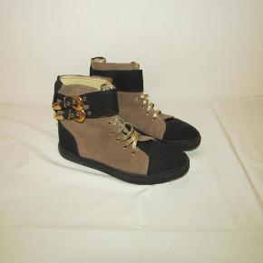 Stine Goya kort støvle i ruskind/lærred med spænder og snørebånd sælges. Farve: sort/brun. Oprindelig købspris: 1.800,-. Støvlerne er kun brugt få gange og er i meget fin stand.