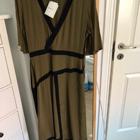 Smuk grøn kjole med et brunligt skær. Den er aldrig brugt.