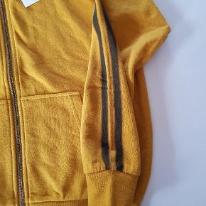 Karrygul hoodie med lynlås og en sort stribe ned langs armen. Ny. Str. 152. Nypris 400 kr.  Køber betaler evt porto. Dao 37 kr.