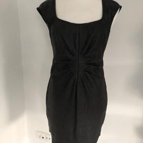 Flot kjole i sort fra Gestuz str. 40 med et lille ærme.  Kjolen har imiteret skind-look både foran og bagpå.  Fin detalje ved maven.  Lukkes i ryggen med skjult lynlås.  Der er en sort underkjole.  Længde fra skulder er 93 cm, brystmålet er 94 cm, og taljen måler 86 cm.  Den ydre del er polyester, og underkjolen er 96% polyester og 4% elastan.  Bærer ikke præg af brug.
