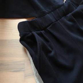 Heldragt fra The New i mørkeblå med stribe i siden. Str 9-10 år. Bukser/t-shirt sidder sammen på midten men ligner lidt et to-delt sæt. Flot stand. Køber betaler fragt