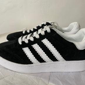 Adidas (Stan Smith - sort med hvide striber & hvid sål) i str 37 (længde 23,5). Aldrig brugt - kun prøvet ifm køb. Købt på rejse, så har derfor ikke æsken! (Sælges for 400 inkl med DAO via MobilePay)