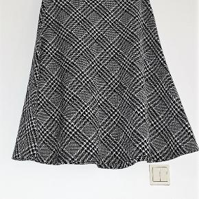 Knæ-lang nederdel i sort/hvid tern, af blødt mellem-tyk strækstof, med elastik i taljen.