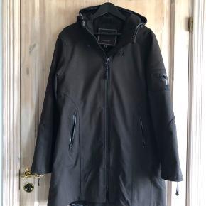 Ilse Jacobsen Rain 07 softshell regnjakke i sort. To-vejs lynlås lukning, raglan ærmer og  3/4 længde. Jakken er i åndbart materiale og har en behagelig pasform der tillader god bevægelse. Jakken er str. 42 og er næsten ikke brugt. Fremstår som ny. Ny pris ca. 1600kr.