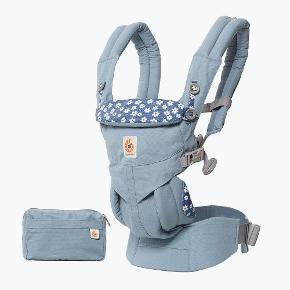 Blå, blomstret Ergobaby Omni 360 bæresele til baby. Pung/lille taske medfølger. Aldrig taget i brug - stadig med mærke. Emballagen haves dog ikke længere. Nypris 1400 kr.  Sælges for minimum 800 kr. Ved forsendelse kommer porto oveni prisen.