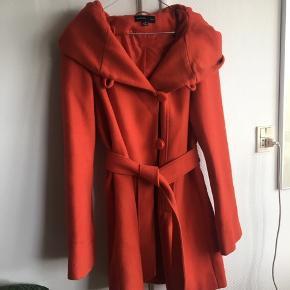Tyk rød frakke med stor hætte og aftagelige bindebånd fra Sara Kelly by Ellos.  Går til midt på lårene.  Brugt men bærer ingen tegn derpå.  Kan ik huske den præcise nypris, men den lå omkring de 2000 kr.  59% Uld 39% Polyester 1% Akryl 1% Polyamid