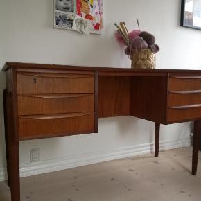 Smukt skrivebord i teak. Har 6 små skuffer og 3 hylder, således  at det også kan stå frit i rummet.