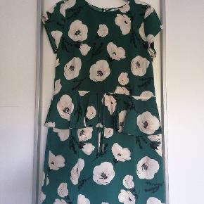 Fin kjole med 'skørt' og bindebånd i taljen. Den er syet om hos skrædder til kort ærme Brystvidde 2x53 cm Længde 94 cm