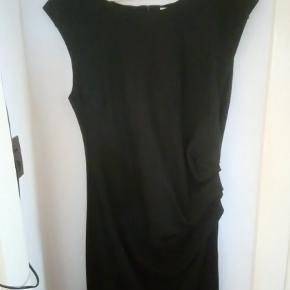 Knælang, let draperet kjole, med lynlås i ryggen.