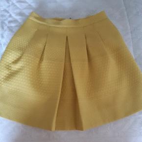 """Smart gul nederdel i kraftigt materiale og sort for. Nederdelen """"strutter"""" når den er på, i samme facon som på billedet."""