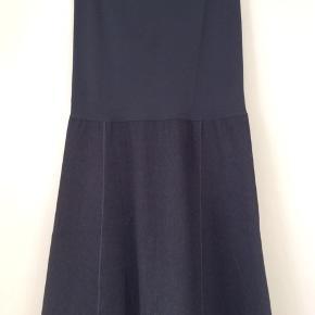 Wolford nederdel/kjole. Materialet er Wool Mix. Den er foret.længde på nederdel fra talje og ned er 54 cm. Elastisk top som er syet på nederdelen 41 cm Brystmål 96-100cm. Talje 79-83 cm Hofte 104-108 cm