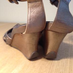 Sandaler, str. 40, KENNETH COLE  Wedges med plateau sandal. Sko med kilehæl.  Str. 40 (9) Hælhøjde 9,5 cm (front 2 cm)  Grå/mokka nuancer i 100% ægte læder med shimmer. Flot og velholdt. Meget lidt brugt. Alle similisten intakte. Similisten er ikke limet på, men fastholdt af en lille bøjle ind i læderet. Meget holdbart. Sidder utrolig godt på foden. Komfortabel og stødabsorberende hæl i gummi.