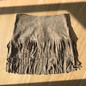 Imiteret ruskind frynse nederdel fra Neo noir. Det er en størrelse xsmall, den er helt ny og stadig med prismærke. Nypris er 500 kr.   Kan sendes på købers regning DAO = 38 kr. Tradono = 32 kr.